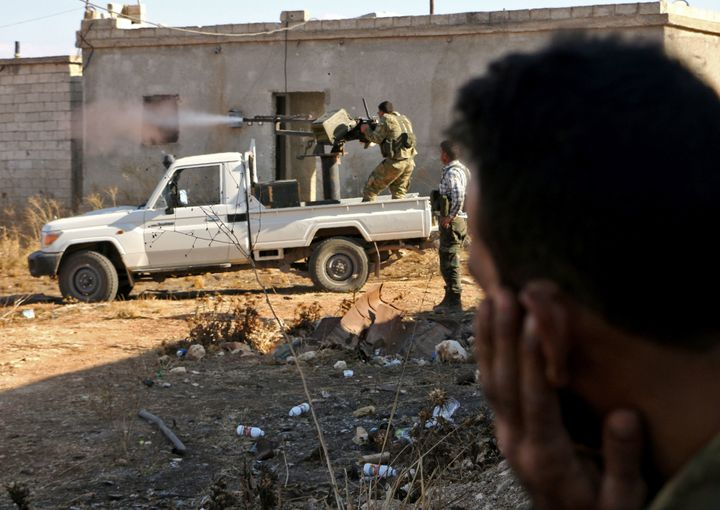 Fighters from the Free Syrian Army fire a machine gun mounted on a vehicle deployed during fighting against the self-describe