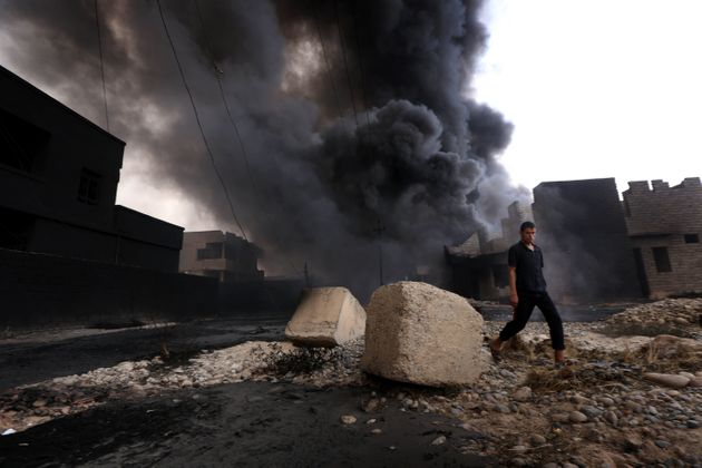 An Iraqi man walks near oil wells set ablaze by Islamic State militants fleeing the oil-producing region...
