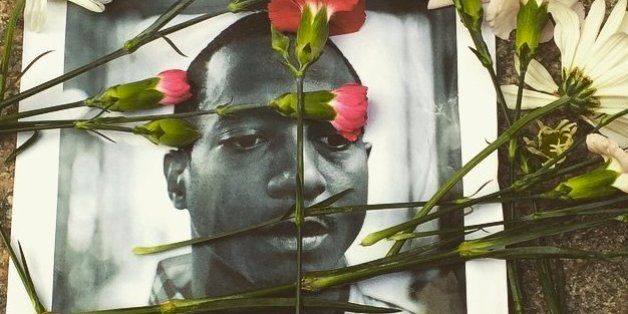 Flowers were strewn across a picture of Kalief Browder during a memorial service and protest over his death in New York City.