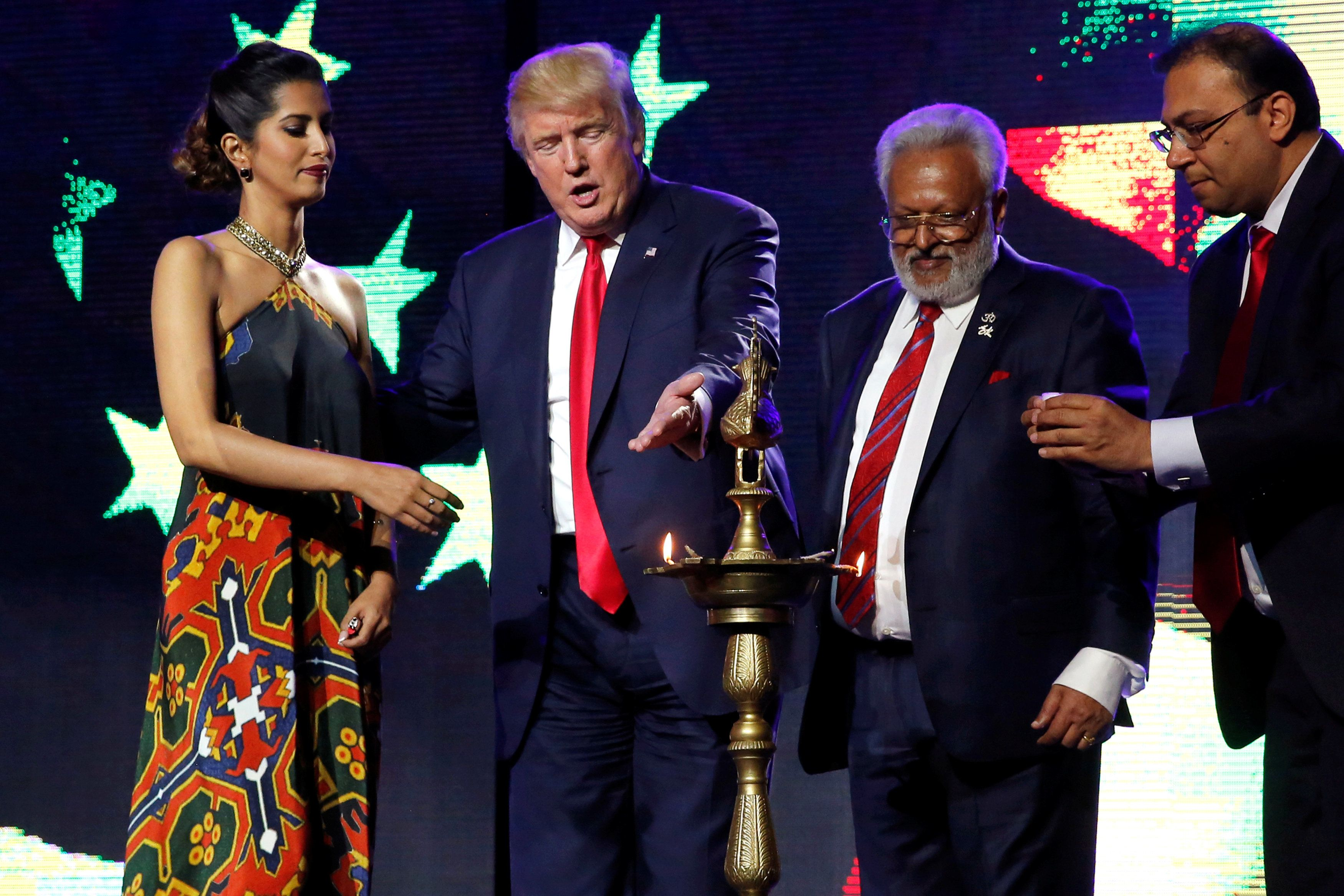 Republican presidential nominee Donald Trump (2nd L) enlists the help of Republican Hindu Coalition Chairman Shalli Kumar (2nd R) and others to light a ceremonial diya lamp before he speaks at a Bollywood-themed charity concert put on by the Republican Hindu Coalition in Edison, New Jersey, U.S. October 15, 2016. REUTERS/Jonathan Ernst