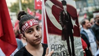 A woman holds a placard picturing Turkisk national flag and Turkey's first president and founder of modern Turkey Mustafa Kemal Ataturk as she takes part in a protest march in Istiklal avenue in Istanbul, on August 30, 2016 during the 94th anniversary of Turkeys Victory Day. Turkish authorities arrested an editor from the leading Hurriyet daily on August 30, continuing a sweep of the media triggered by last month's failed coup, the newspaper said. / AFP / OZAN KOSE        (Photo credit should read OZAN KOSE/AFP/Getty Images)
