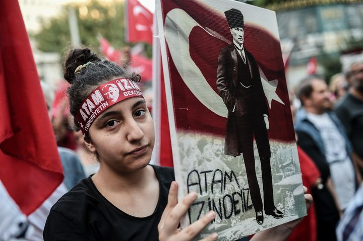 A woman holds a placard picturing Turkisk national flag and Turkey's first president and founder of modern Turkey Mustafa Kem