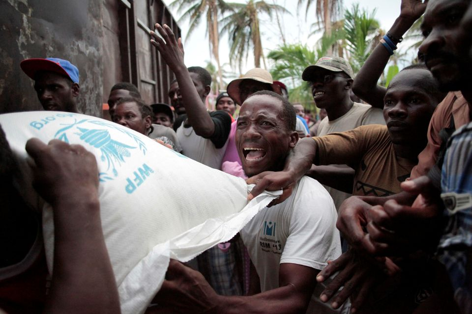 Haitians fight over a sack of rice distributed by humanitarian aid workers after Hurricane Matthew ripped...