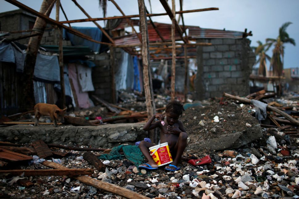 A girl bathes out of a bucket of water next to destroyed houses in Jeremie, Haiti, onOct. 16, 2016.