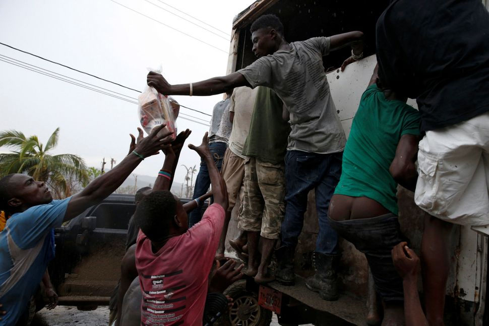 People reach forsupplies from a truckonOct. 14, 2016.
