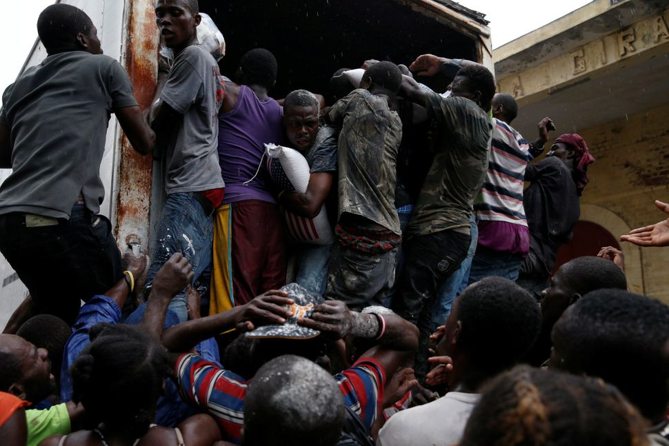 People scramble into a truck with food supplies onOct. 14, 2016.