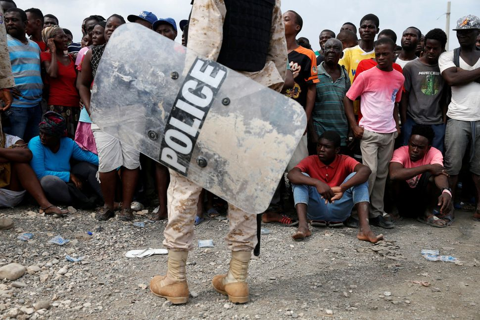 A police officer stands guard in front of the people waiting for the relief aid to be unloaded from a Dutch navy ship on&nbsp