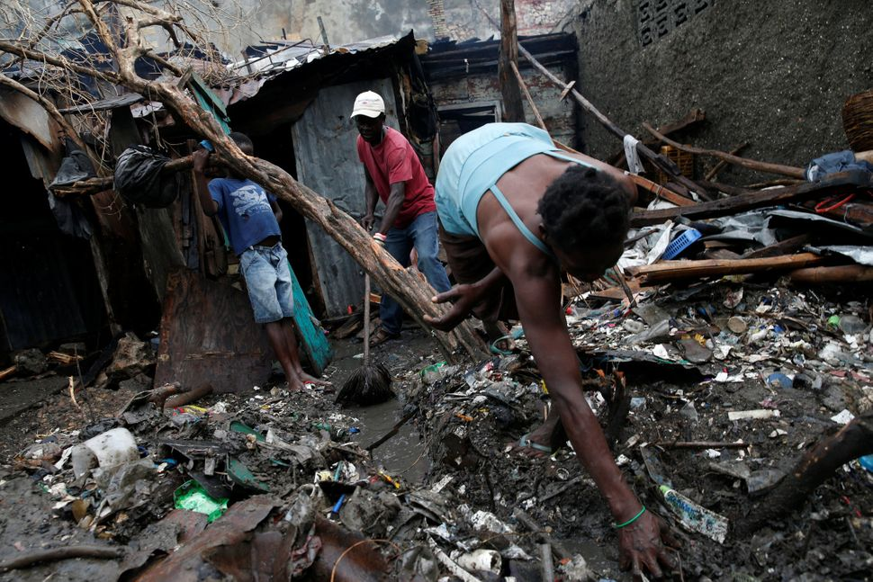 People sort through the wreckage of their destroyed house on Oct. 16, 2016.