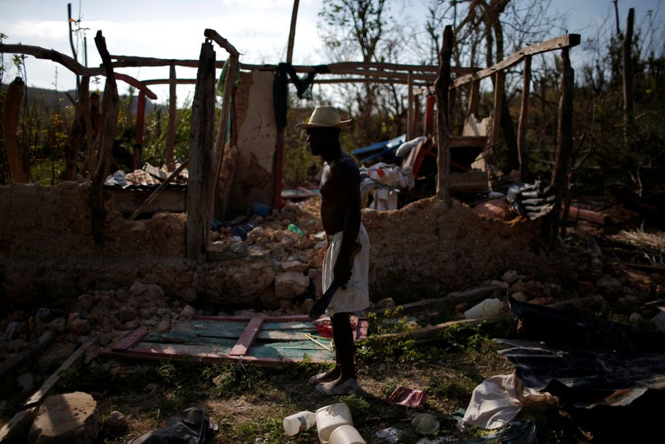 A man stands in front of his destroyed house on Oct. 15, 2016.