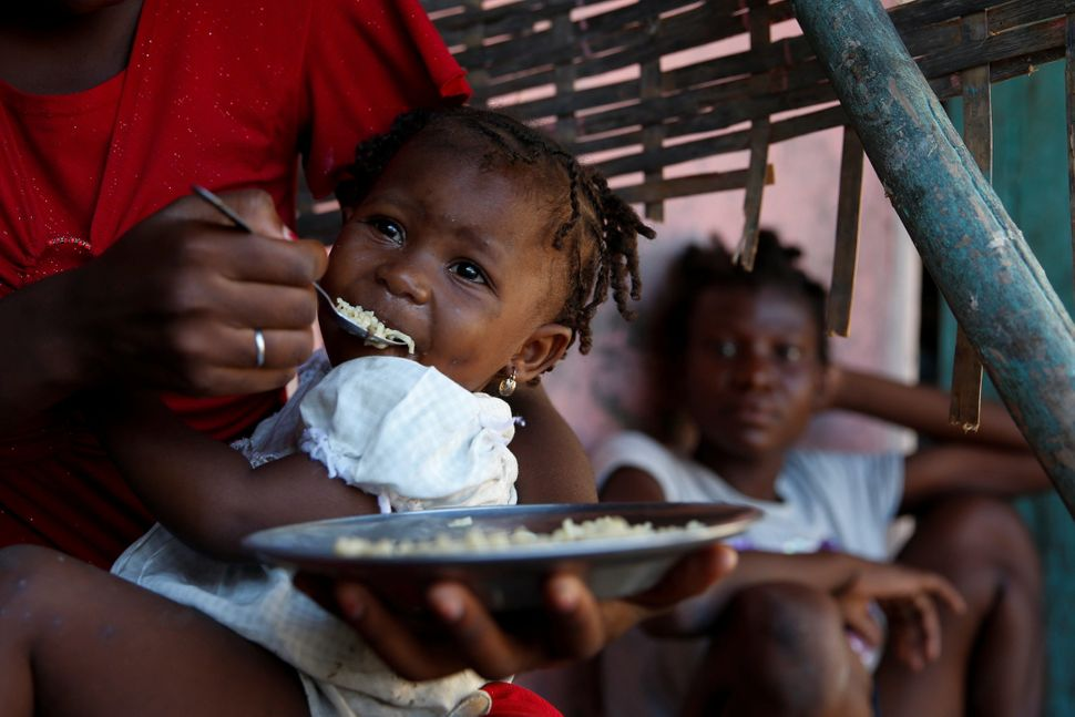 A woman feeds a small girl onOct. 15, 2016.