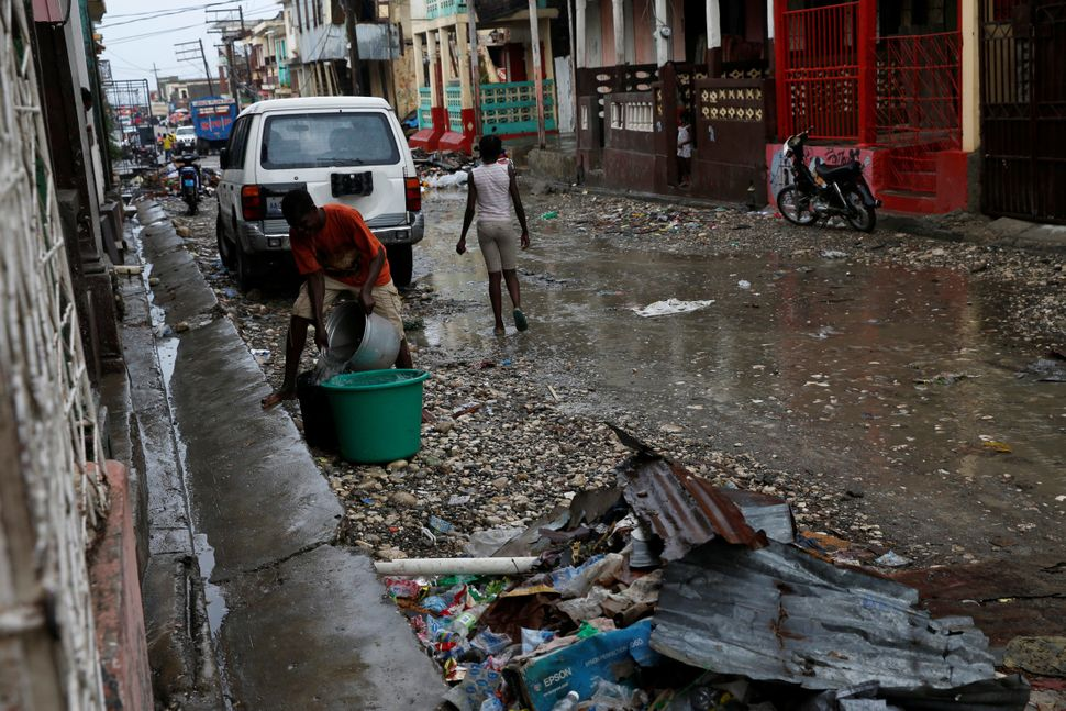 A man collects rain water in a plastic container on the streetonOct. 16, 2016.