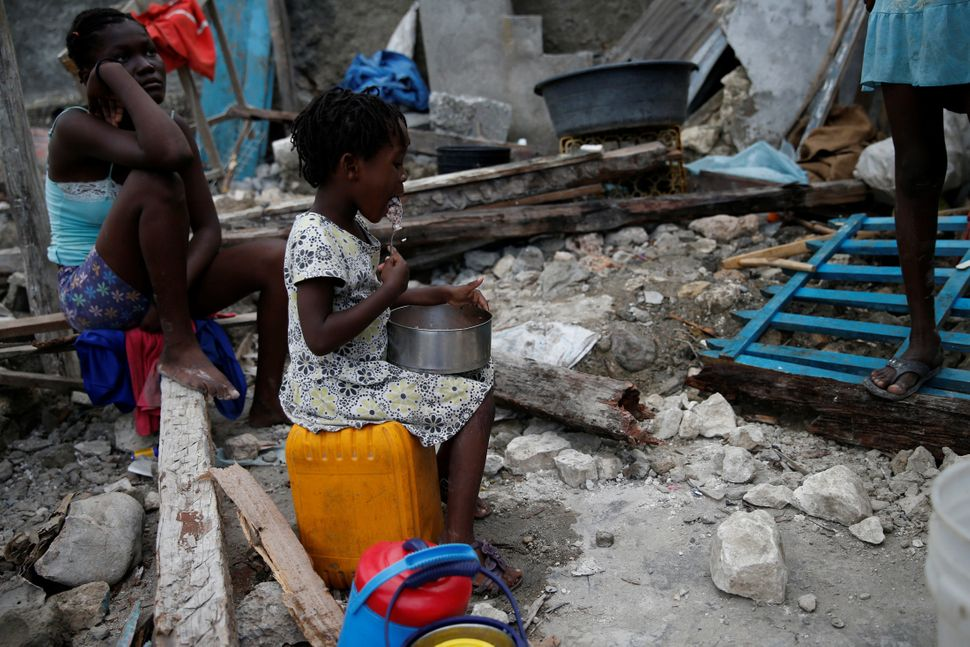 A girl eats at her destroyed house onOct. 15, 2016.