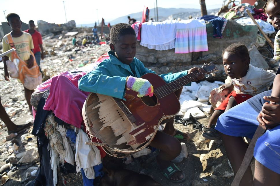 A boy plays with a broken guitar while sitting in rubble on Oct. 8, 2016.