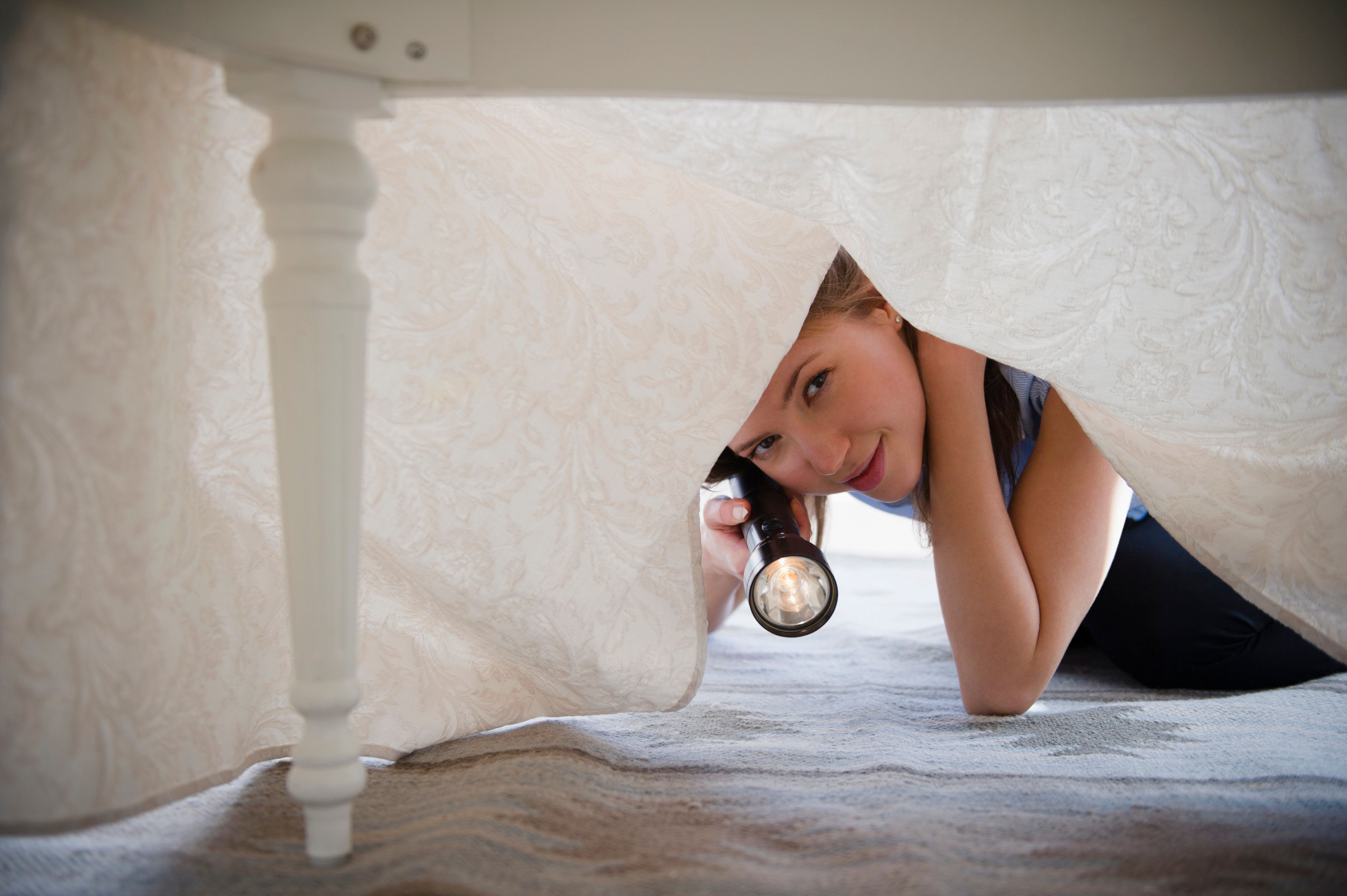 USA, New Jersey, Jersey City, Woman with flashlight looking under bed