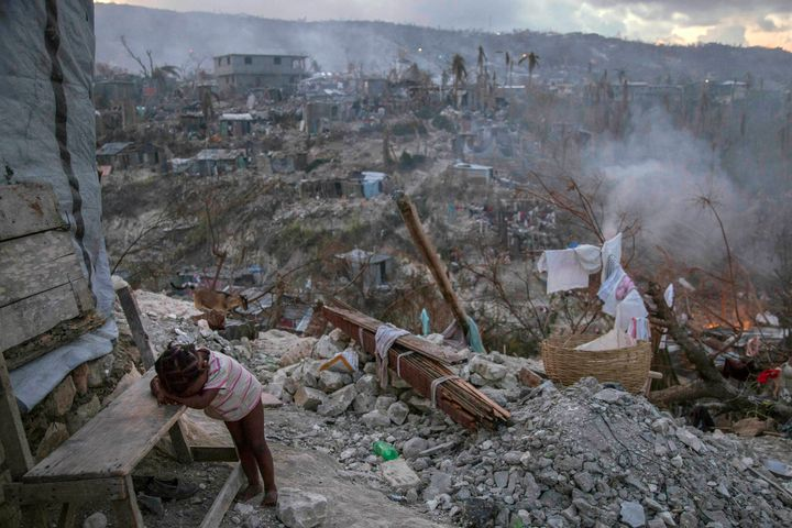 On 10 October 2016 in Jérémie, Haiti, a toddler rests near collapsed homes on top of a hill. One week after Hurricane Matthew