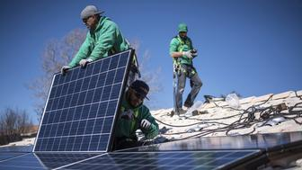 Workers secure solar panels to a rooftop during a SolarCity Corp. residential installation in Albuquerque, New Mexico, U.S., on Monday, Feb. 8, 2016. SolarCity is scheduled to release earnings figures on February 9. Photographer: Sergio Flores/Bloomberg via Getty Images
