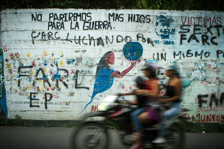 "A mural outside of Toribio Cauca reads, ""We will not give birth to more children for the war."" Below that pronouncement, FARC"
