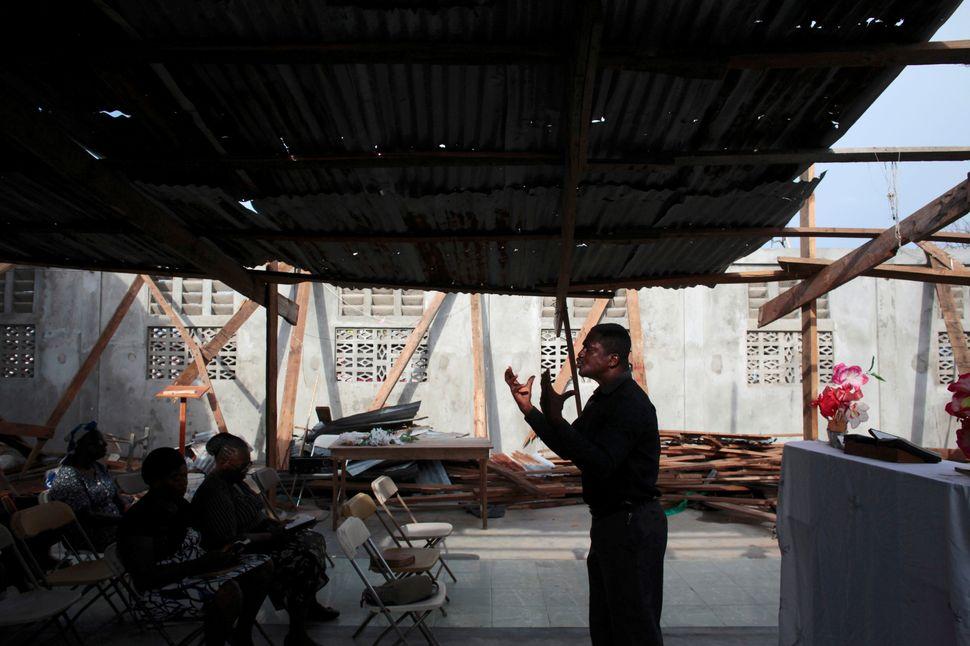 A pastor leads a prayerin a damaged churchonOct. 16, 2016.