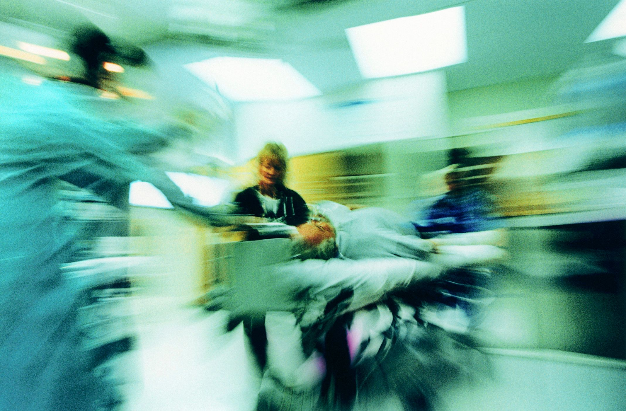 Hospital trauma staff wheeling in patient