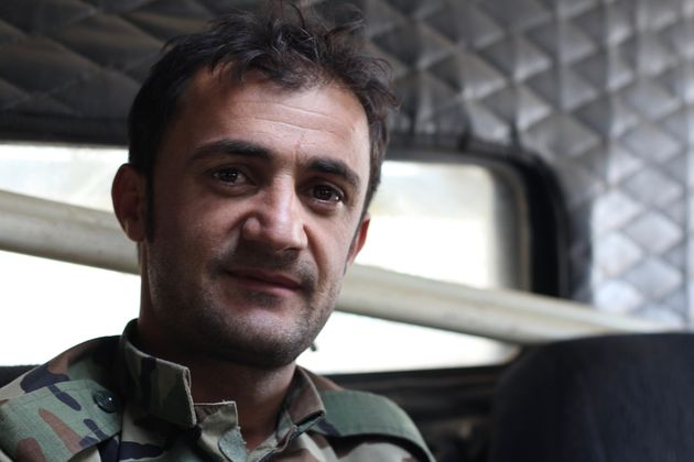 "A Kurdish Peshmerga deminer sits inside of an armored, mine-resistant ""Badger"" vehicle while..."