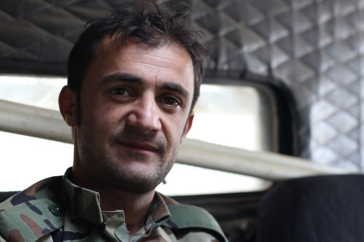 "A Kurdish Peshmerga deminer sits inside of an armored, mine-resistant ""Badger"" vehicle while his colleagues defus"
