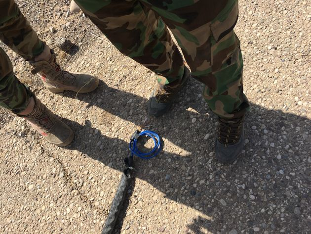 Peshmerga fighters stand next to a defused Islamic State IED meant to explode when a vehicle or person...