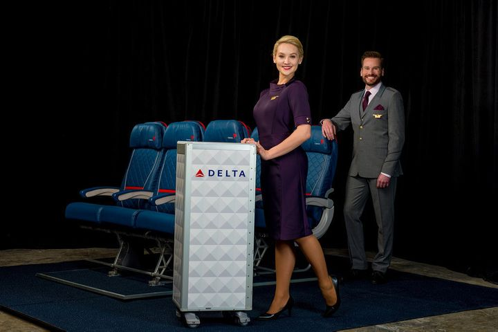 Flight attendant uniforms include a three-button suit with Delta logo-patterned tie and a dresswith matching gloves and handbag.
