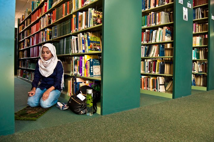 A woman has a quiet moment of prayer in a quiet corner of a library.