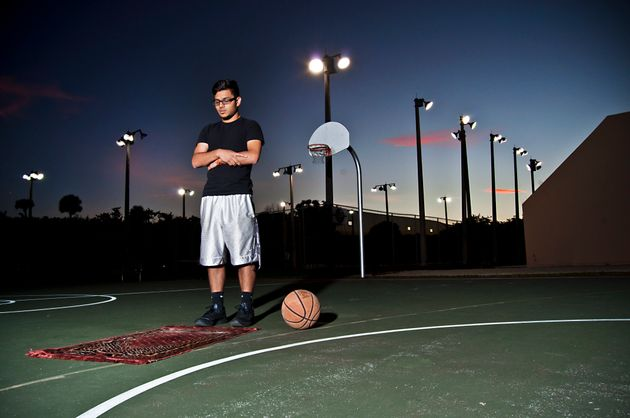 A young man prays on a basketball court in