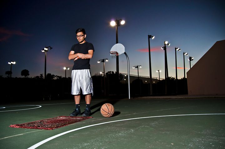 A young man prays on a basketball court in Florida.