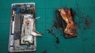 THIS IMAGE HAS BEEN BINNED. A Samsung Note 7 handset is pictured next to its charred battery after catching fire during a test at the Applied Energy Hub battery laboratory in Singapore October 5, 2016. REUTERS/Edgar Su      TPX IMAGES OF THE DAY