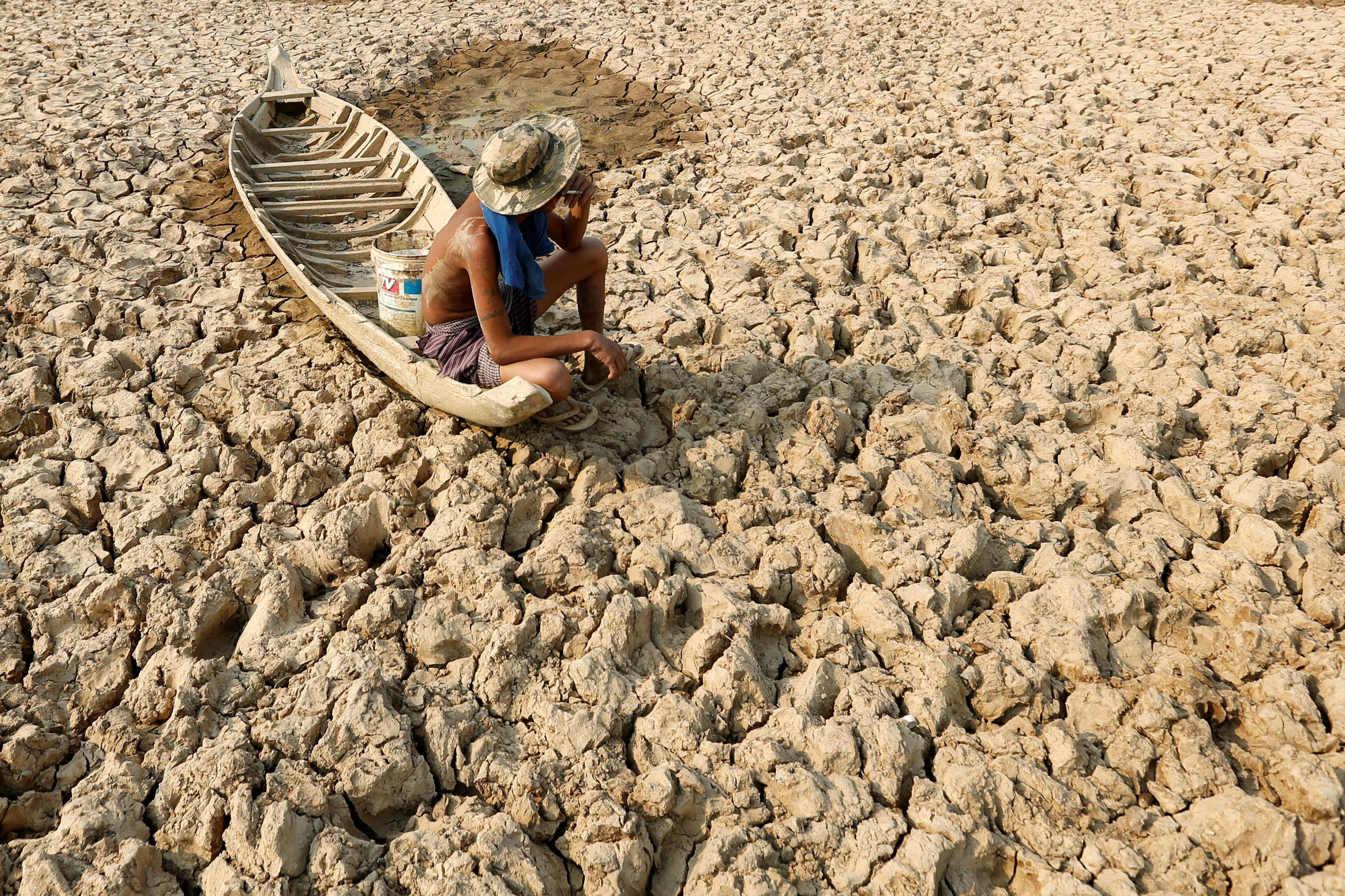 A fisherman sits on his boat in a dried-up pond in drought-stricken Cambodia in May 2016. Climate change...
