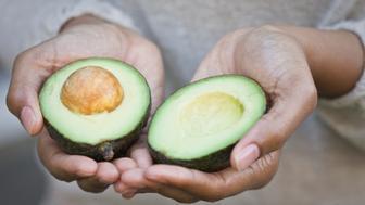 African American woman, holding avocado halves