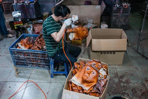 A worker paints a mask of Donald Trump.