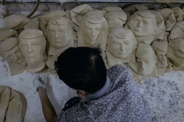 A worker sorts out masks of Donald Trump.
