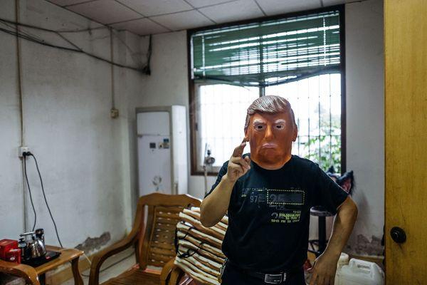 An employee wearing a mask of Donald Trump.
