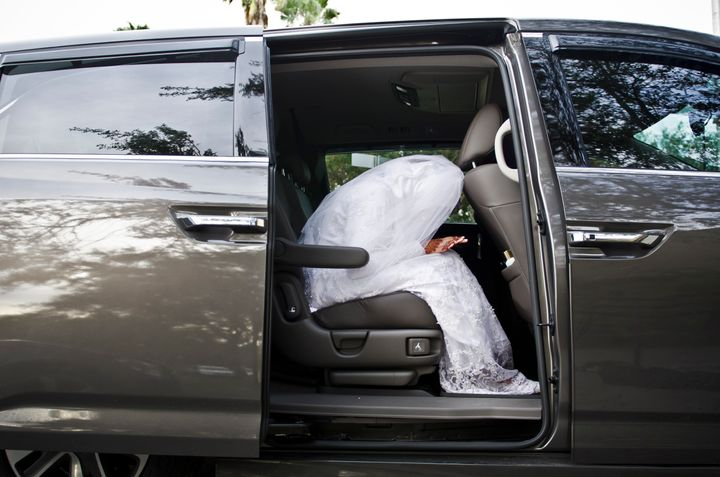 A woman prays in a van on the way to a wedding ceremony.
