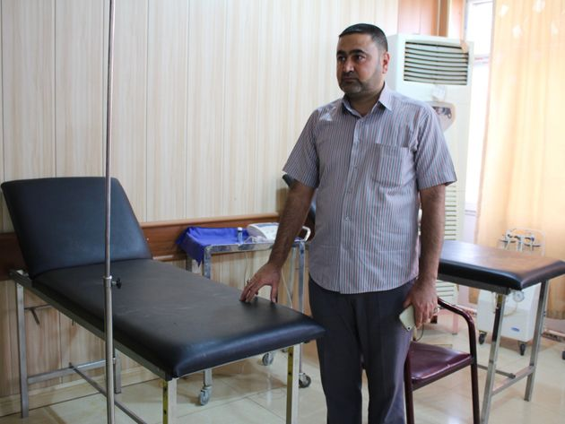 A nurse at the small medical center in Taza, Iraq, stands next to the hospital bed where he tried to...