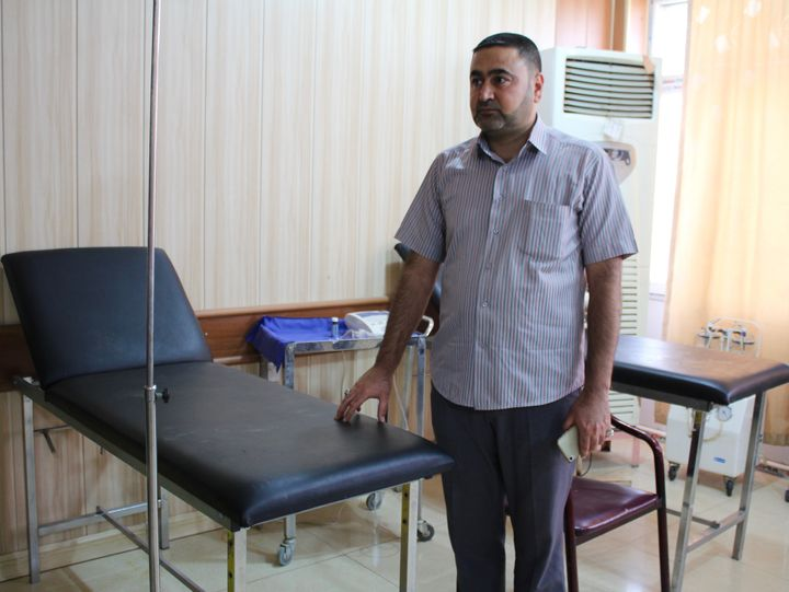 A nurse at the small medical center in Taza, Iraq, stands next to the hospital bed where he tried to save Fatima's life in Ma