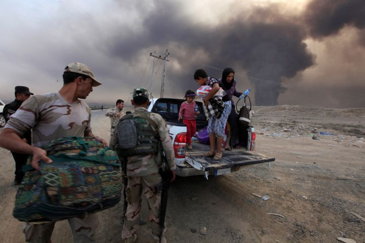 Displaced people who are fleeing from clashes arrive in Qayyarah, during an operation to attack Islamic State militants in Mo