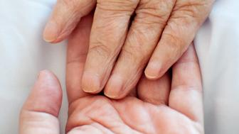 A young hand touches an old wrinkled hand