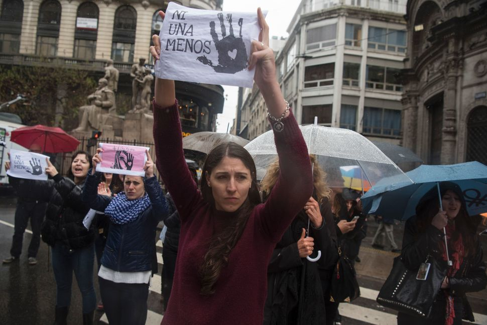 "Women protest in the rain in Buenos Aires with ""Ni Una Menos"" signs."