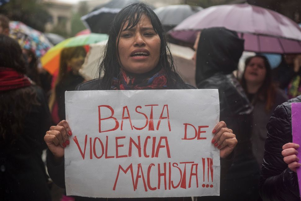 "A woman in Buenos Aires protests with a sign that says ""Stop Sexist Violence."""