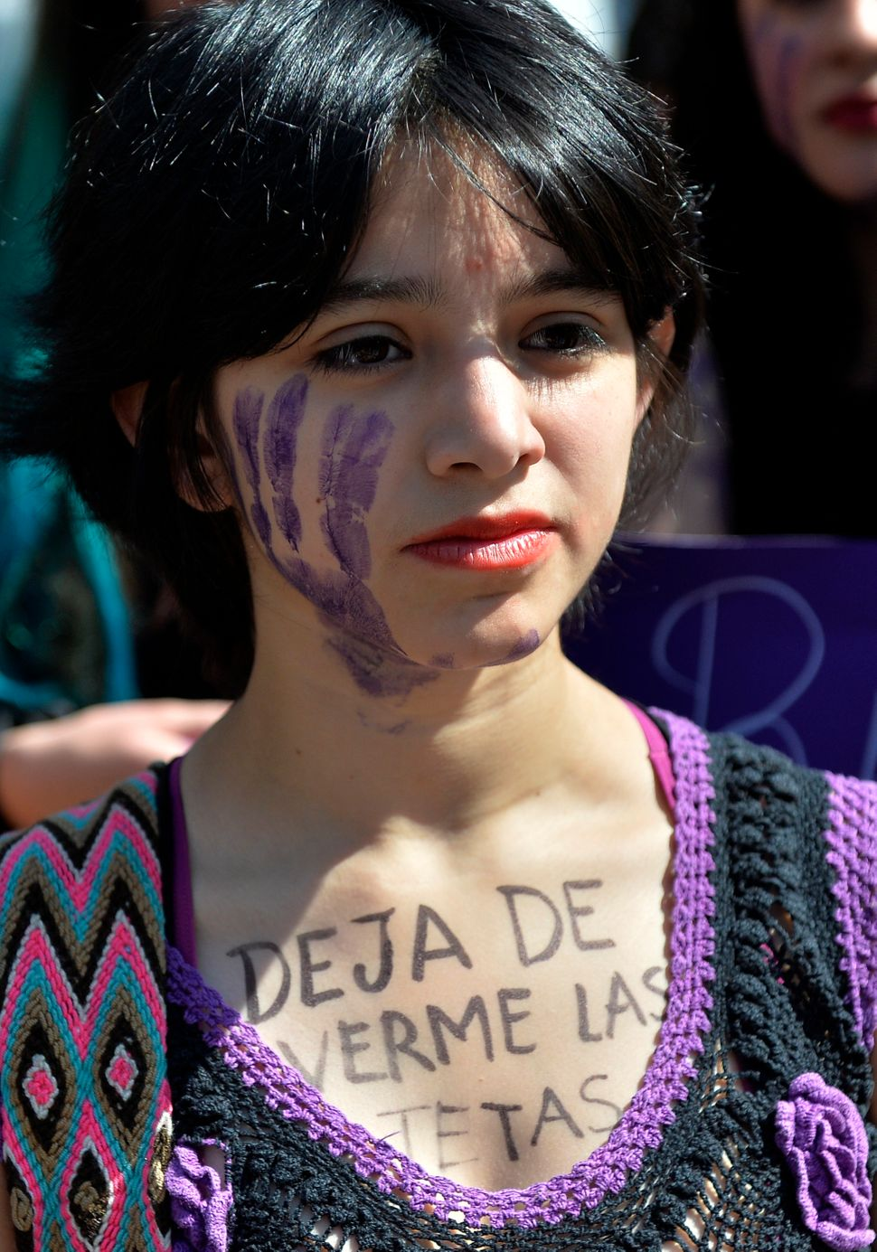 "A woman in Mexico City with the sentence ""Stop Looking at my Breasts"" written on her chest takes part in October 19 protests."