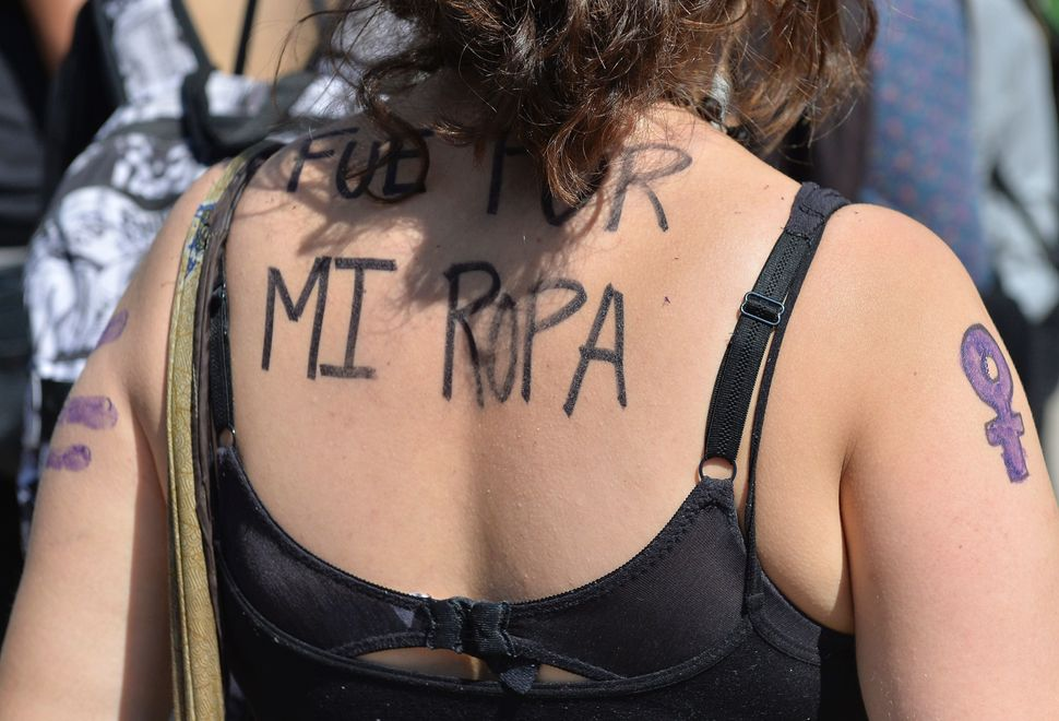 A woman in Mexico City with the sentence 'It Was Because Of My Clothes' written on her back takes part in the October 19 prot
