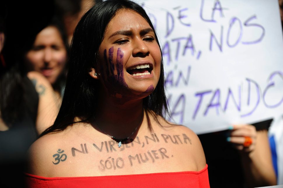 "A woman in Mexico City protests on October 19 with the words ""Not a virgin, not a slut, just a woman."""