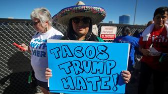 A protestor holds a sign at the Wall of Tacos demonstration in front of the Trump International Hotel Las Vegas before the last 2016 U.S. presidential debate in Las Vegas, Nevada, U.S., October 19, 2016. REUTERS/Jim Urquhart