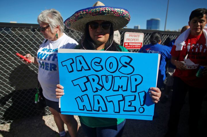 A protestor holds a sign at the Wall of Tacos demonstration in front of the Trump International Hotel Las Vegas on Wednesday.