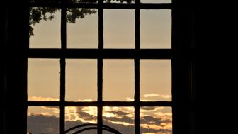 A Unitarian Universalist chalice is silhouetted by the rising sun through a coastal window.