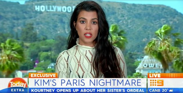 Kourtney stares ahead while being addressed by a